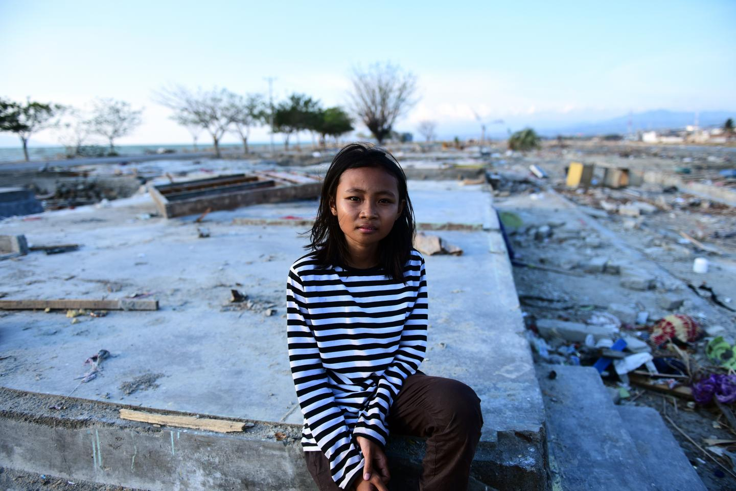 Indonesia earthquake and tsunami. A girl stands by her destroyed house.