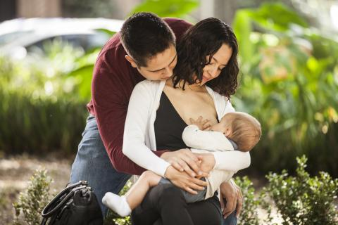 A man supports a woman breastfeeding her child, Mexico