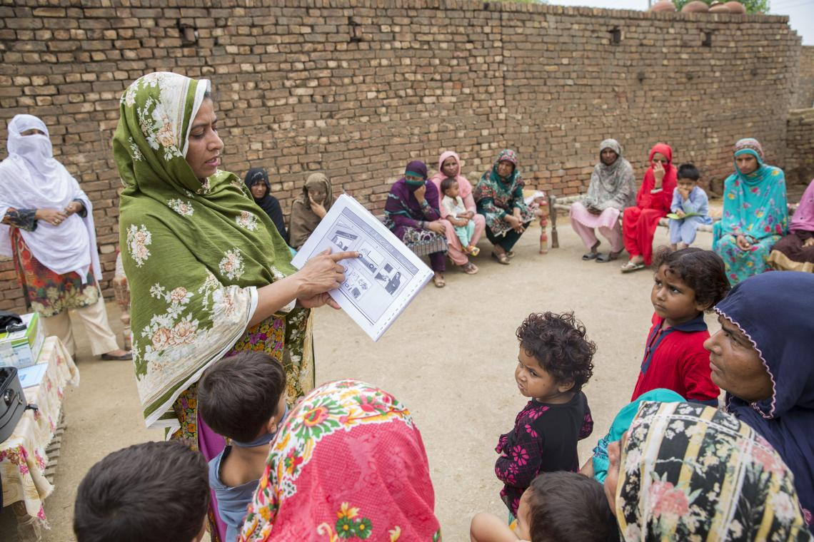 A community health worker talks to a group of women and children, Pakistan