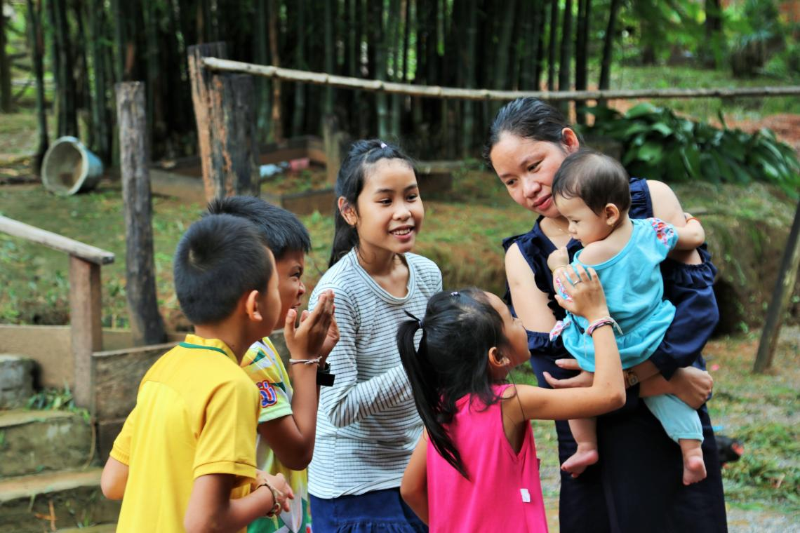 A group of children look at a mother holding an infant, Lao PDR