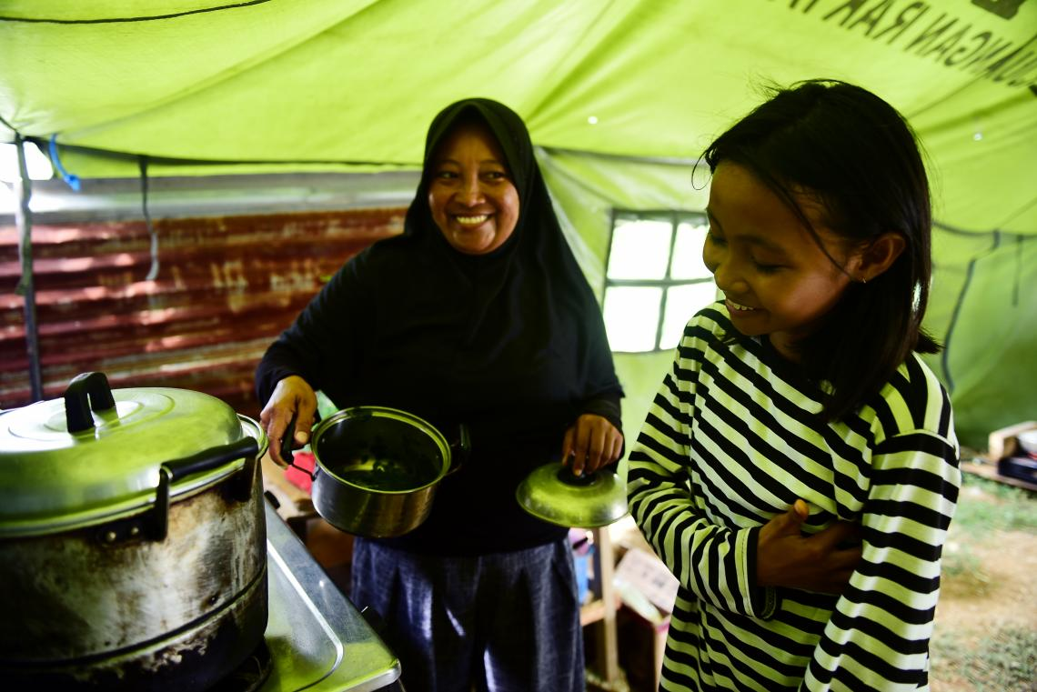 Indonesia earthquake and tsunami. A displaced mother and daughter cook in their temporary shelter.