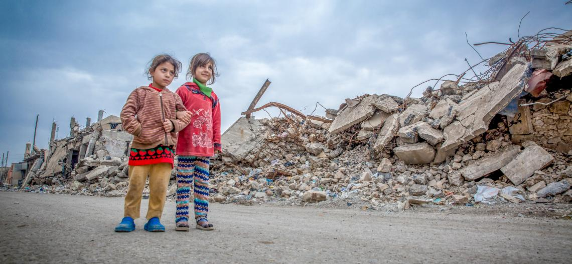 Two children walk where many buildings have been totally destroyed - Mosul, Iraq.